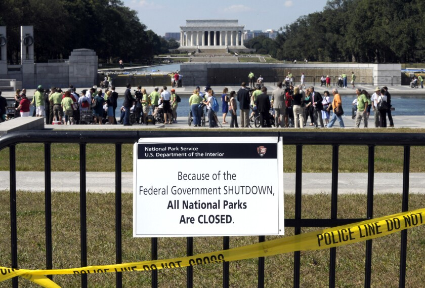 In this Oct. 2 photo people visit the closed World War II Memorial on the National Mall in Washington, despite signs stating that the national parks are closed due to the federal shutdown.