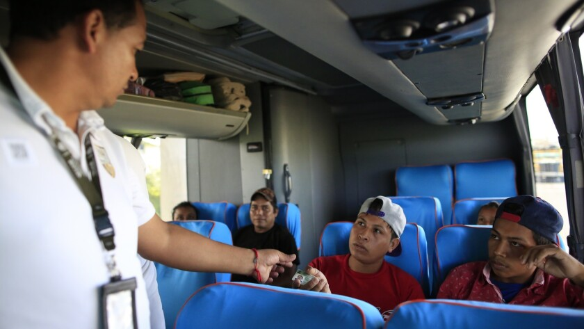 An officer from the National Migration Institute checks travelers' IDs aboard a northbound bus at a