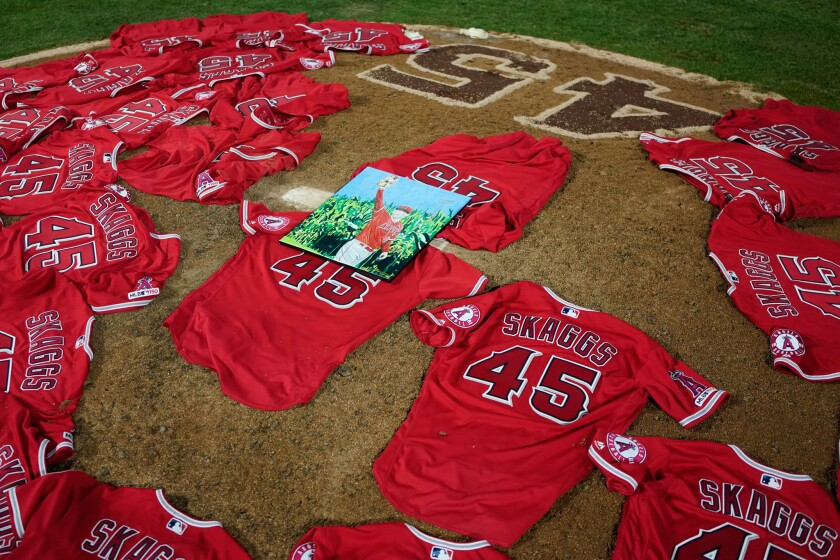 A portrait of the late Angels pitcher Tyler Skaggs sits atop the jerseys on the pitcher's mound at Angel Stadium