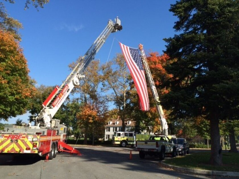 An American flag is draped from two fire trucks during the national memorial ceremony for fallen firefighters in Emmitsburg, Md., Sunday, Oct. 12, 2014. U.S. Rep. Steny Hoyer delivered the keynote address. Among the 107 firefighters honored were 19 Arizona firefighters killed in a 2013 canyon fire and 10 first responders killed in a fertilizer plant explosion in Central Texas last year. Ninety-eight of the firefighters honored died in the line of duty in 2013. Nine died in previous years. (AP Photo/PennLive.com, Ivey DeJesus)