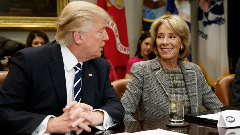 President Donald Trump looks and Education Secretary Betsy DeVos at a meeting with parents and teachers in the Roosevelt Room of the White House on Feb. 14.