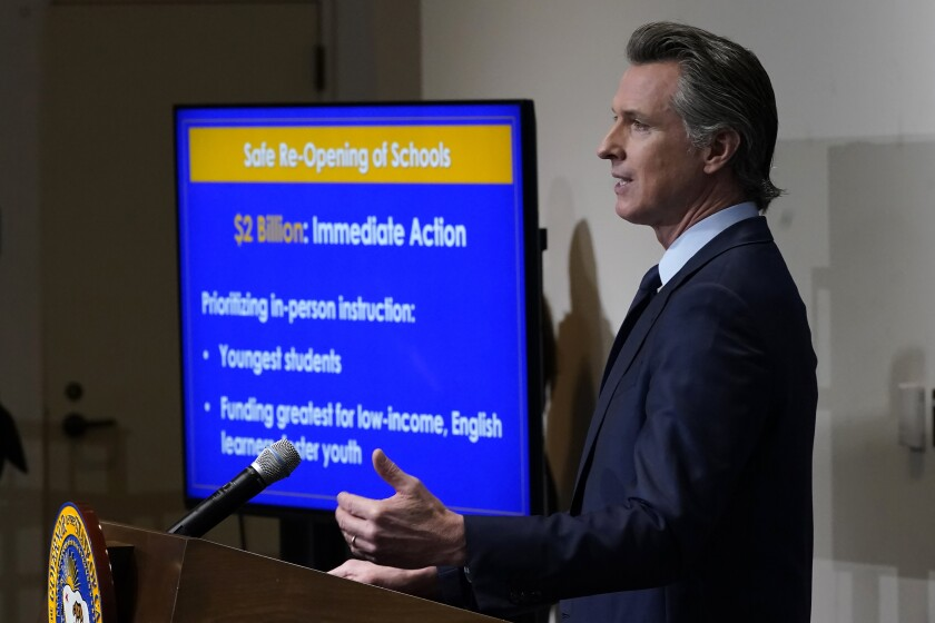 Gov. Gavin Newsom stands at a lectern as a TV shows his 2021-22 state budget proposal.