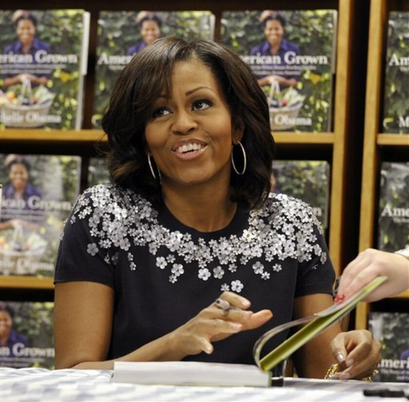 """First lady Michelle Obama signs copies of her book """"American Grown: The Story of the White House Kitchen Garden and Garden Across America"""" at the Politics & Prose bookstore in Washington, Tuesday, May 7, 2013. (AP Photo/Susan Walsh)"""