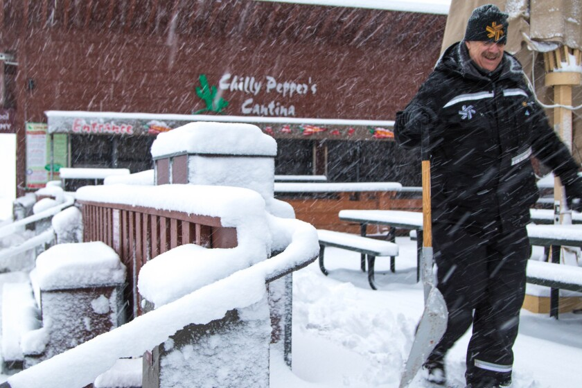 An employee walks through heavy snowfall at Big Springs Resort in Truckee, Calif., as a storm swept through on Dec. 21, 2015.