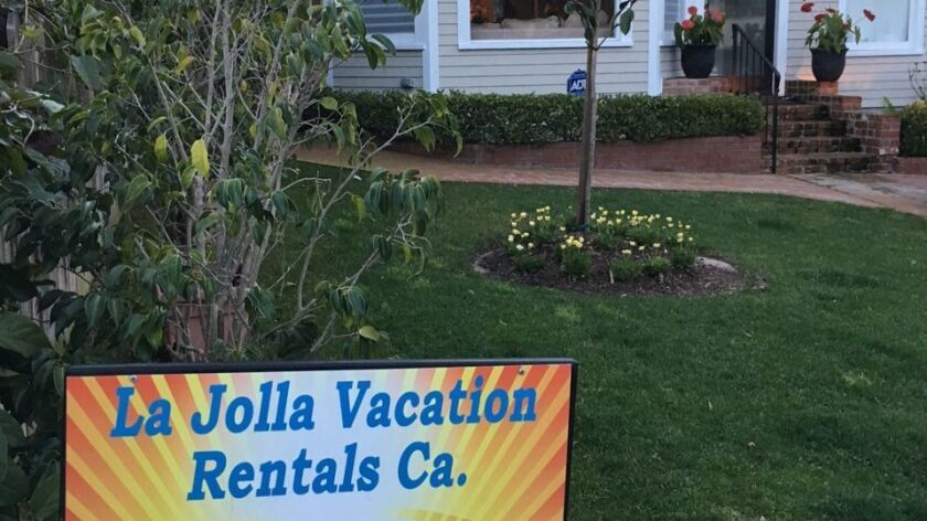 A short-term vacation rental sign is posted in a yard in 2017.