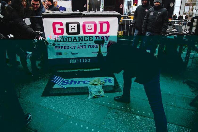 """Los neoyorquinos se estaban deshaciendo hoy de los malos recuerdos del 2016 en el """"Good Riddance Day"""", una ceremonia simbólica en la que se apuntan las ideas negativas en un papel y se destruyen en una trituradora gigante en Times Square. EFE"""