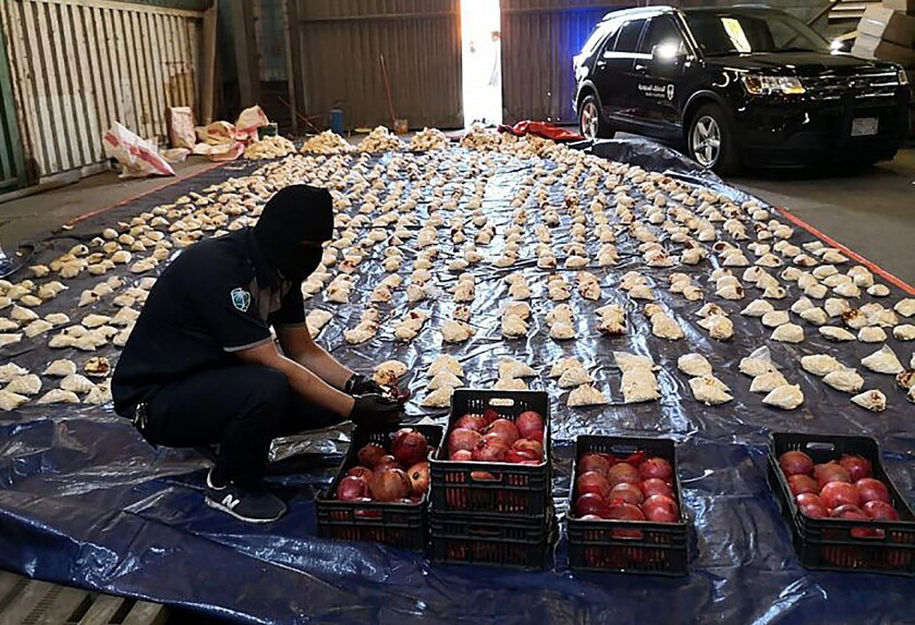 FILE - In this Friday, April 23, 2021 file photo, released by Saudi Press Agency, a Saudi custom officer opens imported pomegranates, as customs foiled an attempt to smuggle over 5 million pills of an amphetamine drug known as Captagon, which they said came from Lebanon, at Jiddah Islamic Port, Saudi Arabia. Lebanon called on Saudi Arabia Monday to reconsider its decision to ban Lebanese produce from entering the oil-rich kingdom over drug smuggling vowing to take strict measures to prevent such acts and investigate the case. (Saudi Press Agency via AP, File)
