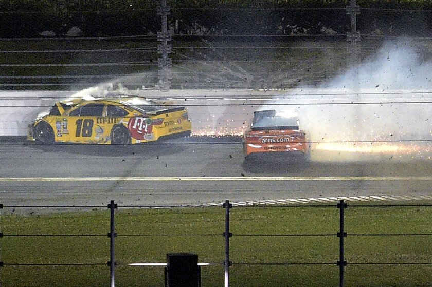 Kyle Busch (18) and Carl Edwards, right, slide along the back stretch after colliding during the Sprint Unlimited auto race at Daytona International Speedway, Saturday, Feb. 13, 2016, in Daytona Beach, Fla. (AP Photo/Phelan M. Ebenhack)