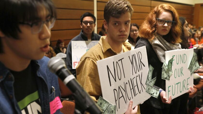 The UC regents plan to vote on an $8.7-billion spending plan for 2018-19 that includes the first tuition decrease in nearly 20 years. Above, UC Berkeley student Calvin Nguyen, left, speaks out against tuition hikes at a UC Board of Regents meeting.