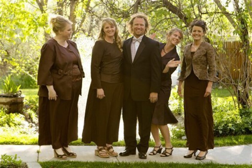 """FILE - In this undated file photo provided by TLC, Kody Brown, center, poses with his wives, from left, Janelle, Christine, Meri, and Robyn in a promotional photo for TLC's reality TV show, """"Sister Wives."""" The Browns' attorney, Jonathan Turley, says he will file a lawsuit in Salt Lake City's U.S. District Court on Wednesday, July 12, 2011, challenging the Utah bigamy law that makes their lifestyle illegal. (AP Photo/TLC, Bryant Livingston, File)"""