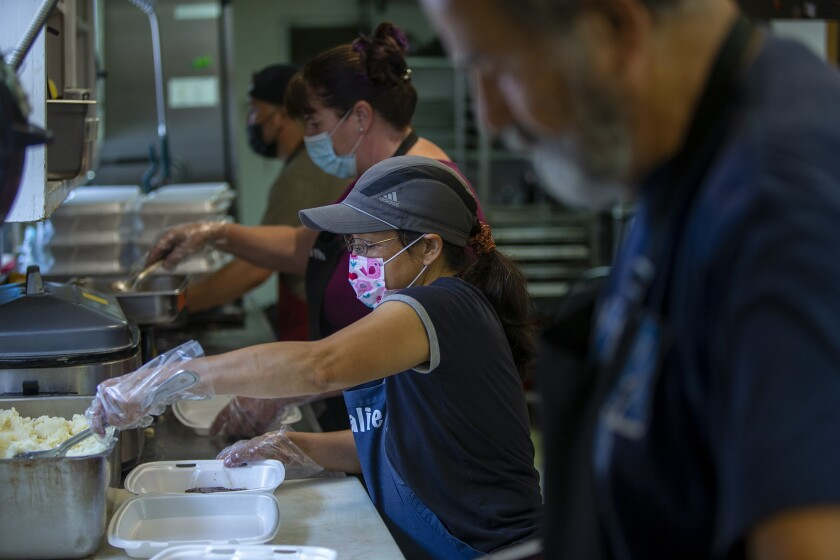 Natalie Wolf, center, and other volunteers prepare meals for the homeless at Mary's Kitchen in Orange on Tuesday, July 13.