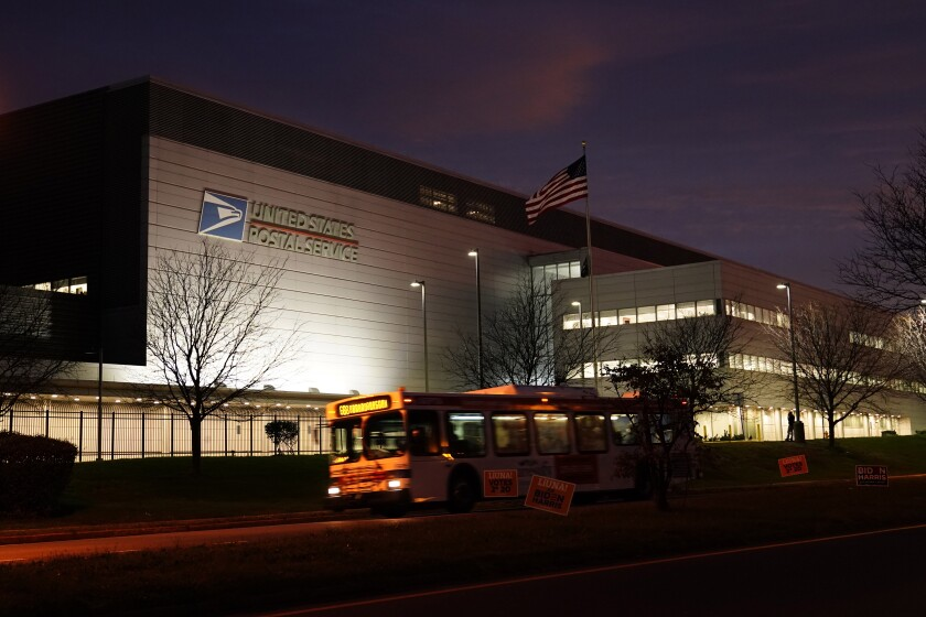 A bus drives past a United States Postal Service facility, Tuesday, Nov. 3, 2020, in Philadelphia. Concerns about mail delivery delays prompted a federal judge to order postal workers in major cities to sweep processing facilities for any remaining ballots before the end of the day. (AP Photo/Matt Slocum)