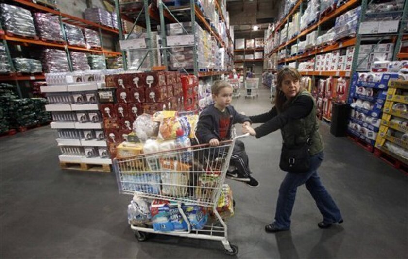 FILE - In this Dec. 7, 2011 file photo, Tina VanPelt and her son Soloman, 4, shop at a Costco wholesale store, in, Portland, Ore. Wholesale businesses barely increased their stockpiles in November, even though their sales grew strongly. (AP Photo/Rick Bowmer, File)