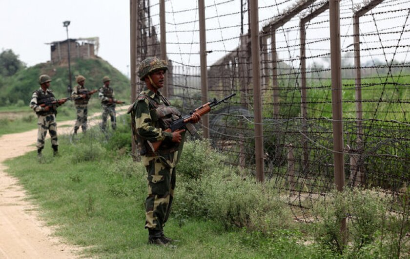 Indian soldiers stand guard along fencing near the Chachwal outpost along the border between India and Pakistan.
