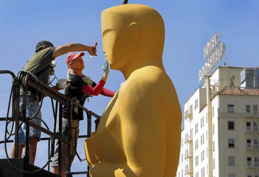 Lead scenic artist Dena D'Angelo, right, and scenic artist Rick Roberts use sand paper to prepare the giant Oscar statue for gold paint before he makes an appearance on the red carpet.