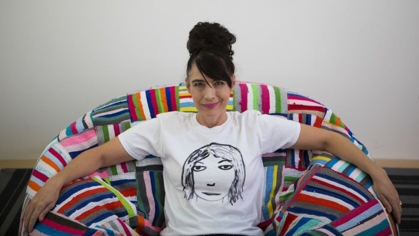 Kathleen Hanna sporting a T-shirt of Kim Gordon's face from her Tees 4 Togo line.