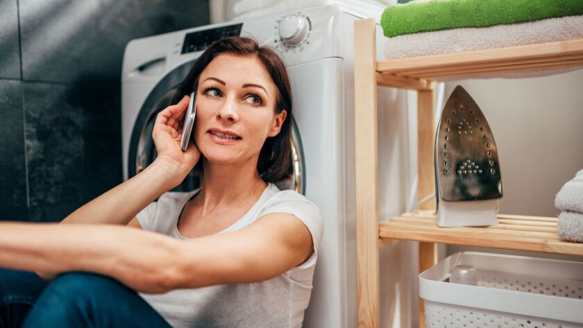 Woman talking on smart phone at laundry room