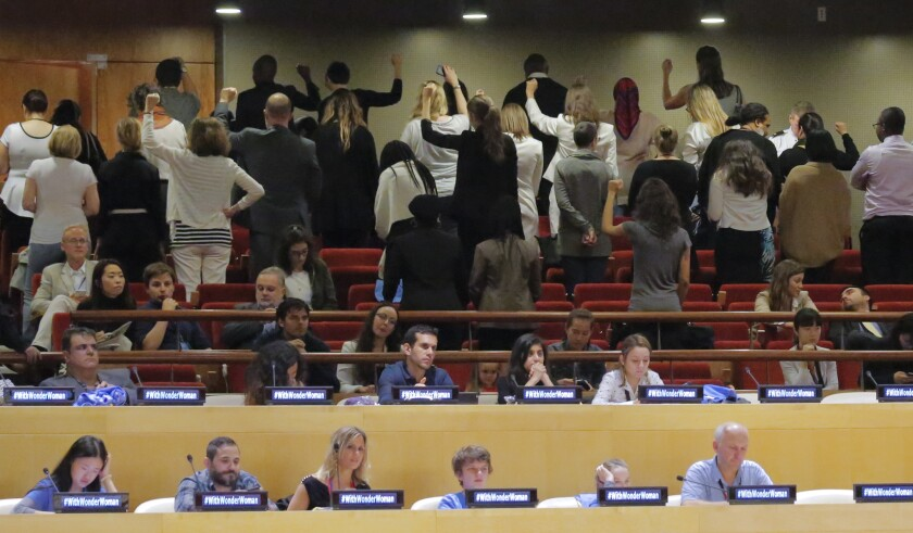 United Nations staff members turn their backs in protest during an event where the Wonder Woman character was designated as an Honorary Ambassador for the Empowerment of Women and Girls.