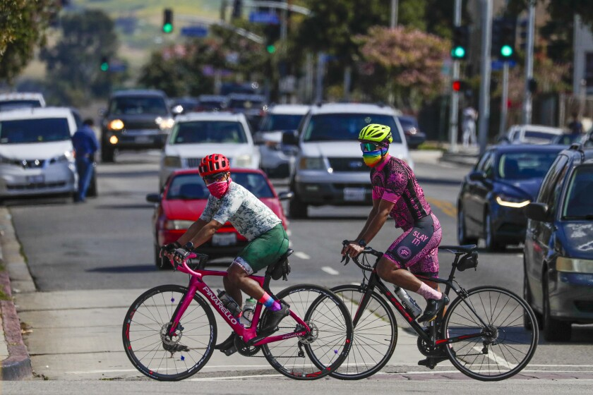 Two cyclists wearing face masks on Cesar E. Chavez Blvd in Los Angeles.
