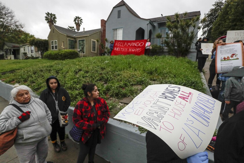 """A group of homeless and housing insecure protesters and their supporters hold a rally on Sheffield Avenue on Saturday to """"reclaim"""" a vacant home."""