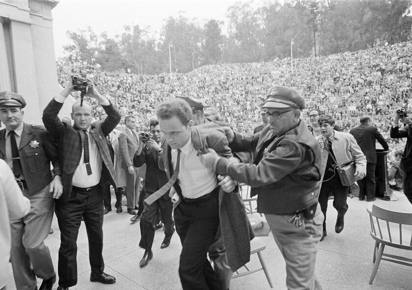 FILE - In this Dec. 7, 1964 file photo, Mario Savio, leader of the Berkeley Free Speech Movement, is restrained by police as he walks on to the platform at the University of California's Greek Theater in Berkeley, Calif. Savio attempted to speak directly following the appearance of University Presi