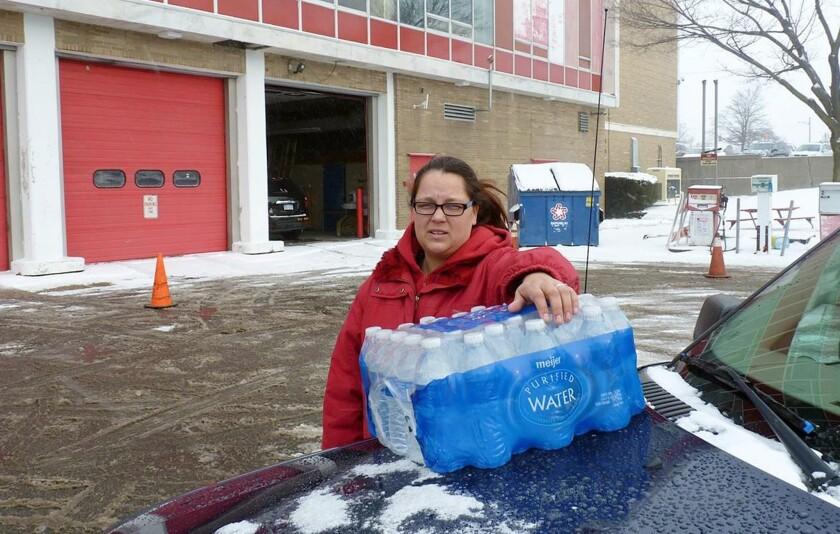 Rebecka Cordell transporta varias botellas de agua para beber afuera de la estación de bomberos en Flint, Michigan. El agua es repartida gratuitamente para que la gente no beba el líquido que sale de los grifos de su casa porque está contaminada con diversas sustancias y plomo. El cineasta documentalista Michael Moore pretende que el presidente Barack Obama visite Flint para que conozca en persona la crisis del agua en la localidad. (AP Foto/Roger Schneider)