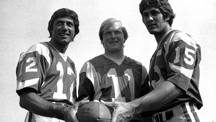 Rookie Vince Ferragamo (15) poses with veteran Rams quarterbacks Joe Namath (12) and Pat Haden (11) during training camp in 1977.