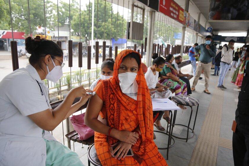 Una trabajadora de la salud administra una dosis de la vacuna contra el COVID-19 durante una campaña especial de vacunación impulsada por la municipalía, en una parada de bus en Ahmedabad, India, el 17 de septiembre de 2021. (AP Foto/Ajit Solanki)