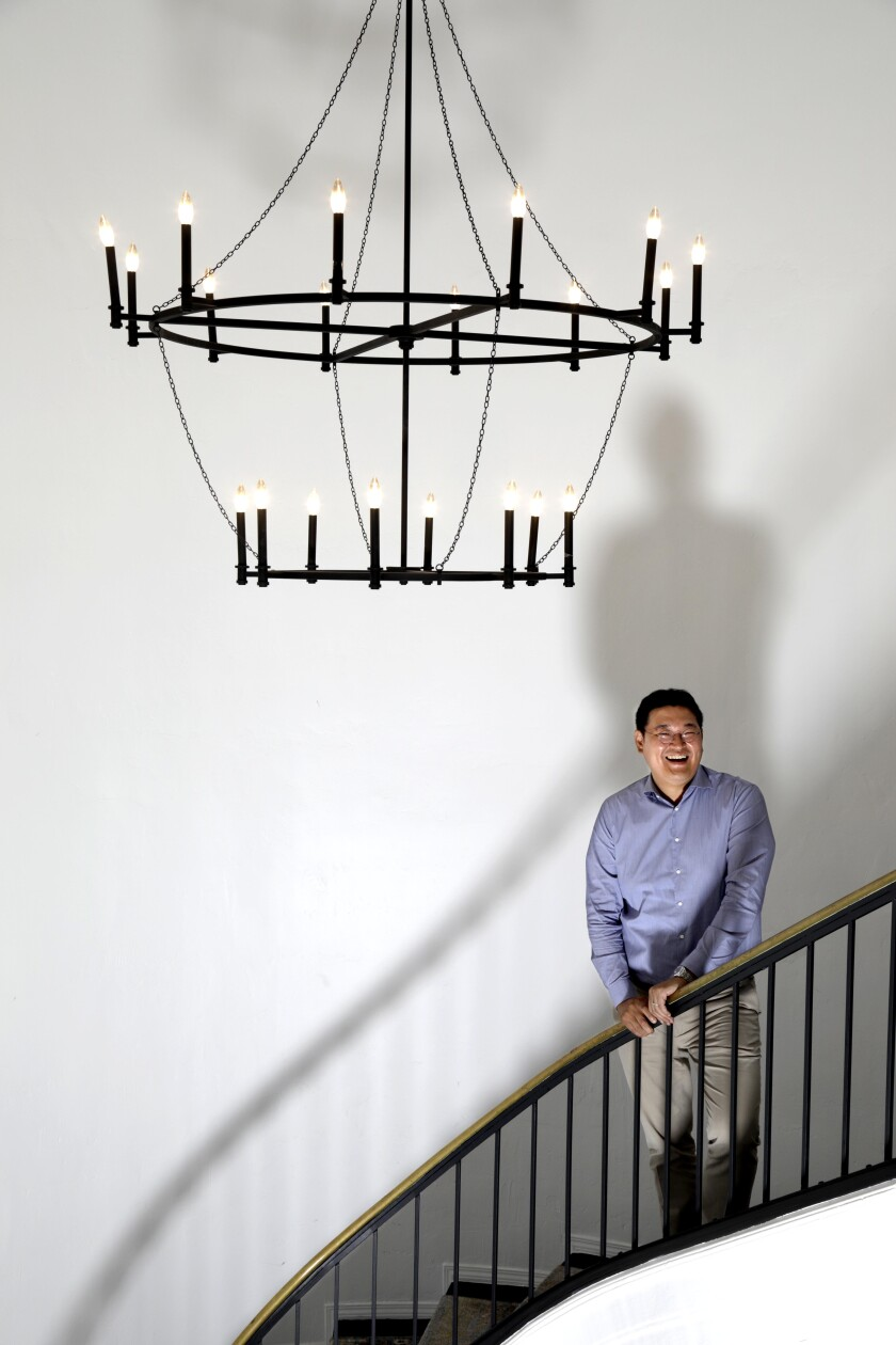 A man in a button-down shirt stands on a staircase at Wiip, a Hollywood production company.