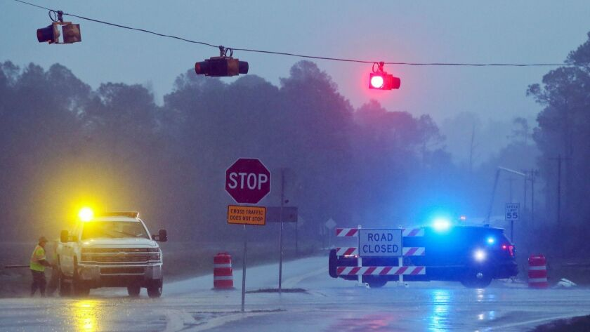 Authorities in Brooks County, Ga., block Highway 122 on Sunday as power line workers repair a downed pole.