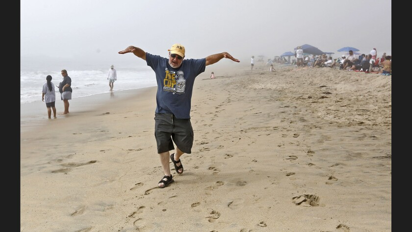 A man pretends to be an airplane as people wait Friday for the Breitling Huntington Beach Airshow practice to start. The practice was called off because of the marine layer.
