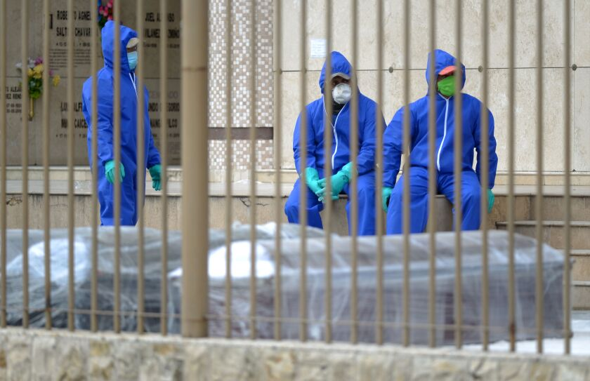 Workers in protective suits wait next to coffins in pandemic-stricken Guayaquil, Ecuador