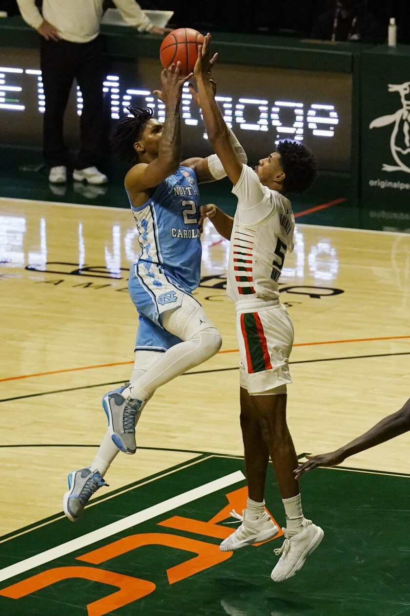 Miami guard Harlond Beverly (5) stops a drive to the basket by North Carolina guard Caleb Love (2) during the second half of an NCAA college basketball game, Tuesday, Jan. 5, 2021, in Coral Gables, Fla. (AP Photo/Marta Lavandier)