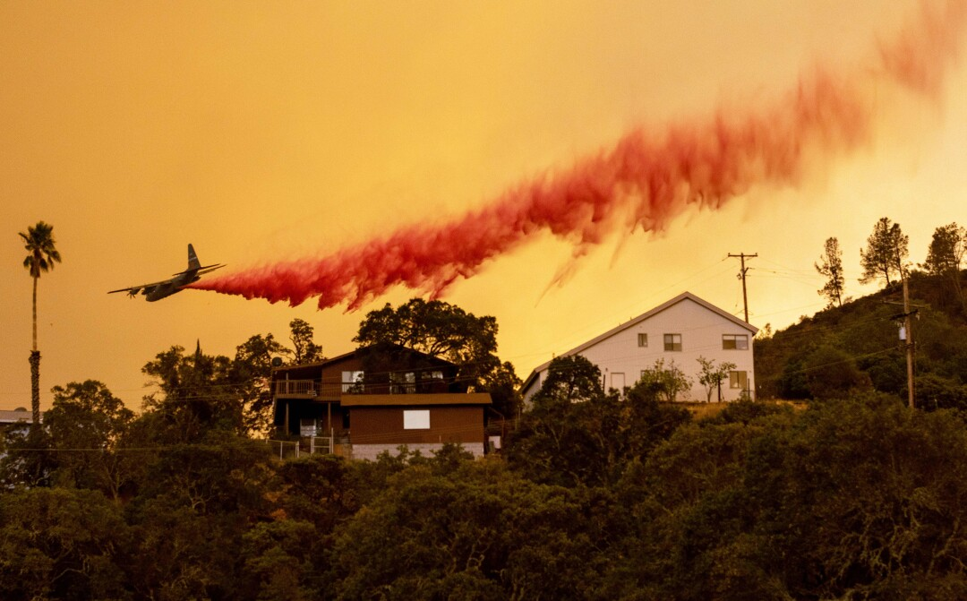 An airplane drops fire retardant over homes in Napa County.