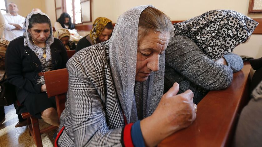 Assyrian Christians, who fled unrest in Syria and Iraq, attend Mass.