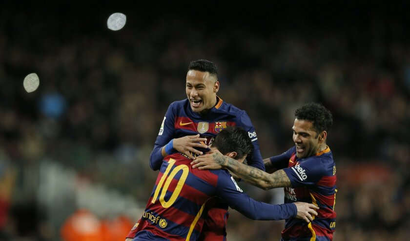 FC Barcelona's Lionel Messi, left, reacts after scoring with his teammates Neymar, center, and Daniel Alves, against Celta Vigo during a Spanish La Liga soccer match at the Camp Nou stadium in Barcelona, Spain, Sunday, Feb. 14, 2016. (AP Photo/Manu Fernandez)