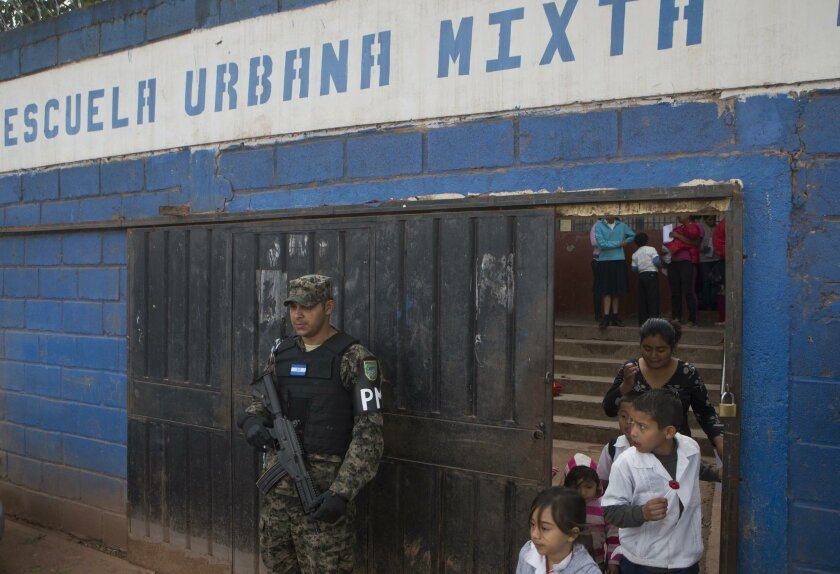 In this photo Nov. 28, 2014 photo, a member of Hondura's Military Police, stands guard at the entrance of a school, during the last day of class, in the Canaan neighborhood of Tegucigalpa, Honduras. Street gangs control most schools in Tegucigalpa, where a lot of the students are gangsters, along w