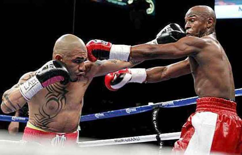 Miguel Cotto, left, and Floyd Mayweather Jr. trade punches during their bout Saturday night in Las Vegas.