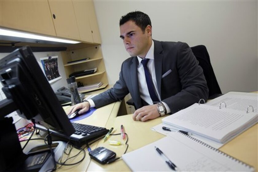 In this Wednesday, Aug. 1, 2012 photo, New York Stock Exchange Senior Compliance Associate Matthew Pizzo, an Air Force veteran who has law and business degrees, works in his office at the New York Stock Exchange. Pizzo had gone two years without work, until recently, as he is now finishing his first week of work at the exchange. U.S. employers added 163,000 jobs in July, a hopeful sign after three months of sluggish hiring. (AP Photo/Richard Drew)