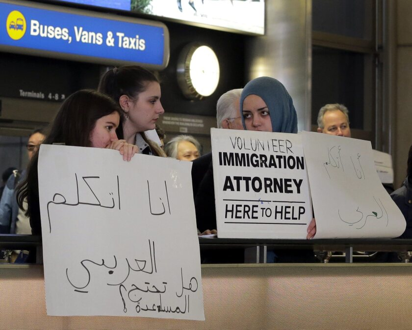 Immigration lawyers offer help to travelers arriving at the Tom Bradley International Terminal at Los Angeles International Airport.