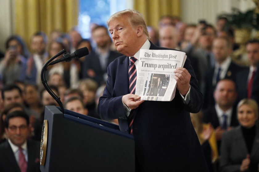 "President Trump holds up a Washington Post with the headline ""Trump acquitted"" as he speaks in the East Room of the White House on Feb. 6."