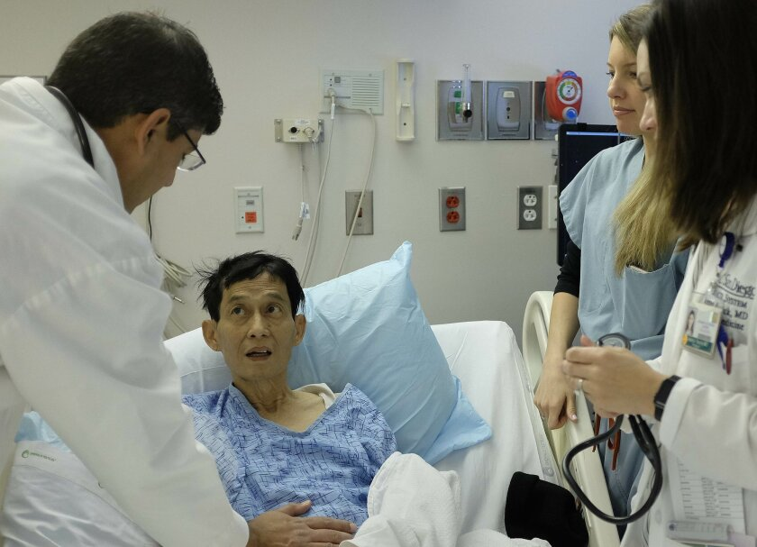 Dr. Rohit Loomba, left, checks on the abdomen of liver patient Ching Year in his hospital room at UCSD Medical Center in Hillcrest.