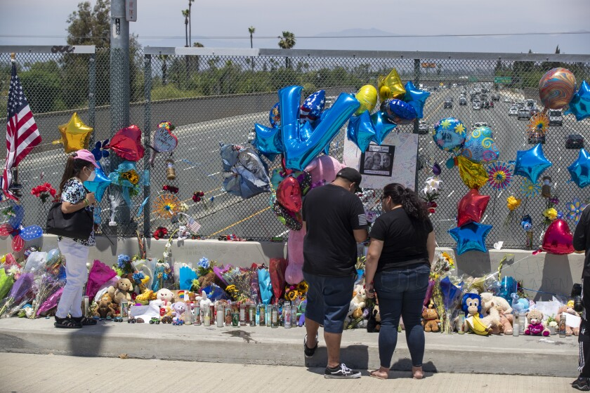 People stand in front of a memorial for 6-year-old Aiden Leos, who was fatally shot Friday on the 55 Freeway in Orange.