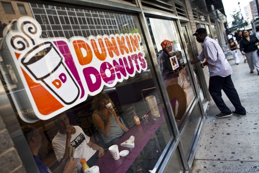 A customer enters a Dunkin' shop.
