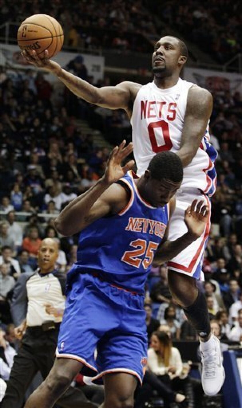 Brooklyn Nets' Andray Blatche (0) drives past New York Knicks' Henry Sims (25) during the second half of a preseason NBA basketball game, Wednesday, Oct. 24, 2012, in Uniondale, N.Y. The Knicks won 97-95. (AP Photo/Frank Franklin II)