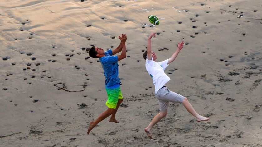CARLSBAD, August 10, 2017 | Two teenage boys try to catch a football as they and others play footbal
