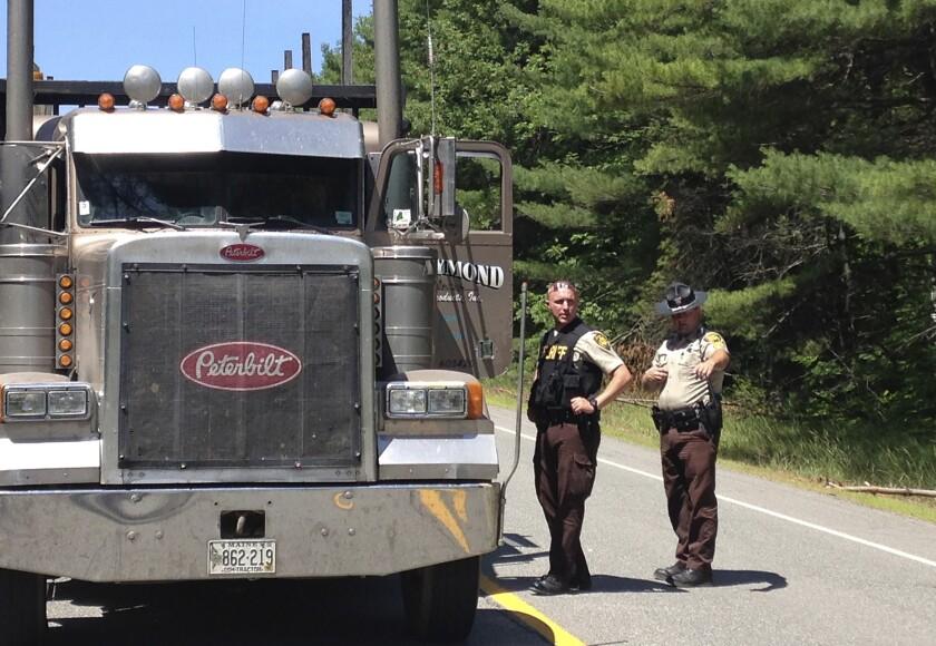 Oficiales del condado de Penobscot hablan con el chofer de camión en un punto de revisión el 17 de julio de 2015 en Lee, Maine. La policía buscaba a un pistolero en un camión maderero robado después de dispararle a cuatro personas durante la noche en los pueblos de Lee, Benedicta y Silver Ridge al norte de Maine. (Foto AP/Alanna Durkin)