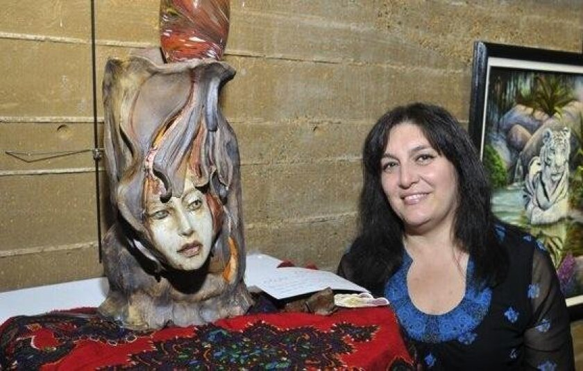 """Lily Pourat poses near her statue during a recent exhibit at the Encinitas Library. """"If I'm not creating, it feels like I'm not living,"""" she said."""