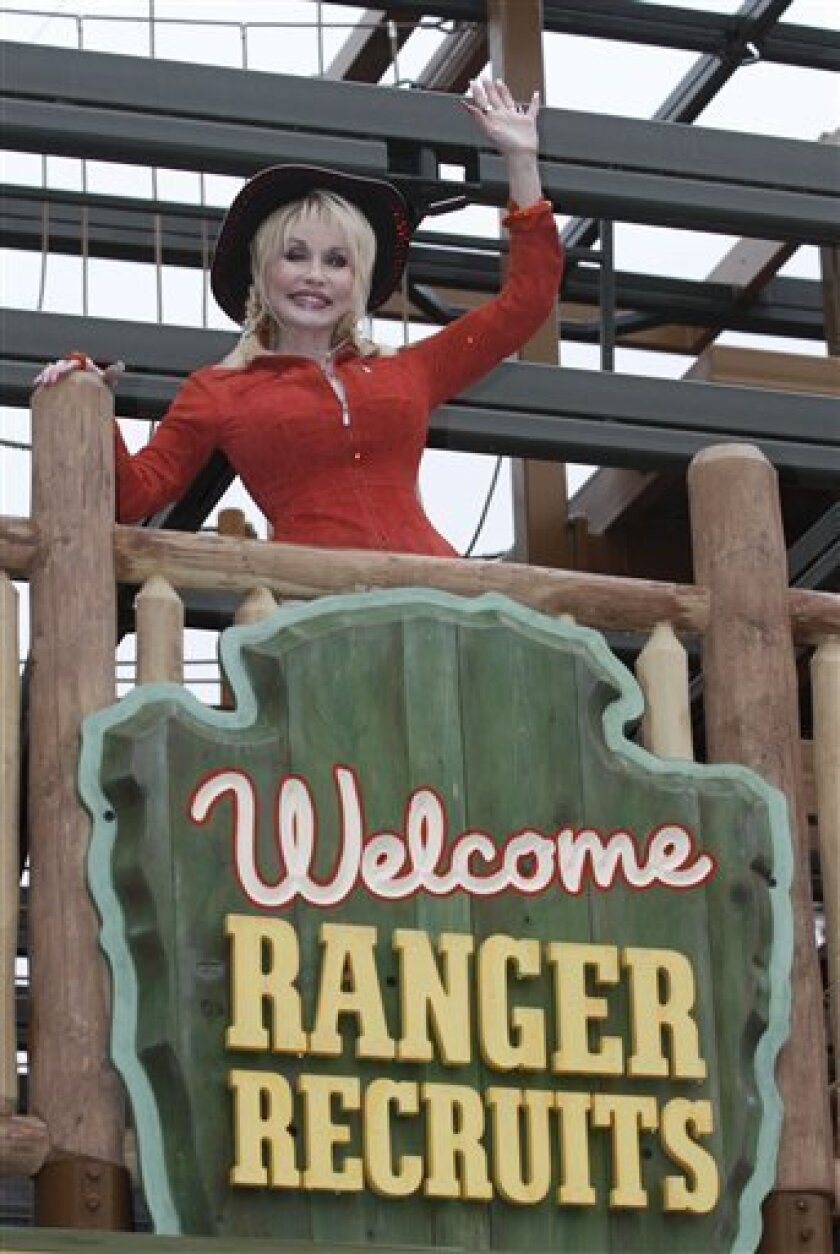 Dolly Parton waves to guests at her latest attraction, Adventure Mountain, during the 25th anniversary celebration of the Dollywood Theme Park, Friday, March 26, 2010 in Pigeon Forge, Tenn.  (AP Photo/Wade Payne)