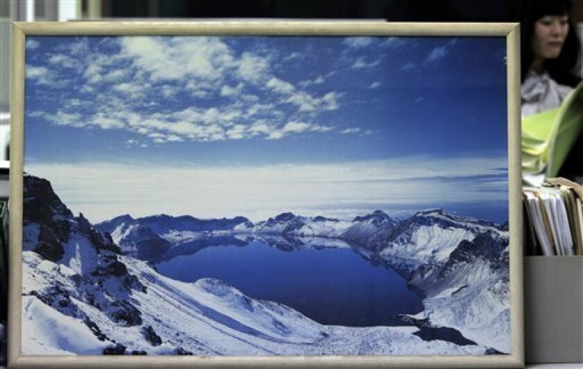 A framed picture of the Cheonjiyeon Lake on the Paektu Mountain in North Korea, is displayed at an office of Korean Council for Reconciliation and Cooperation in Seoul, South Korea, Tuesday, March 22, 2011. South Korea accepted North Korea's proposal to hold talks on conducting joint research on volcanic activity at the North's highest Paektu mountain, officials said Tuesday.(AP Photo/Ahn Young-joon)